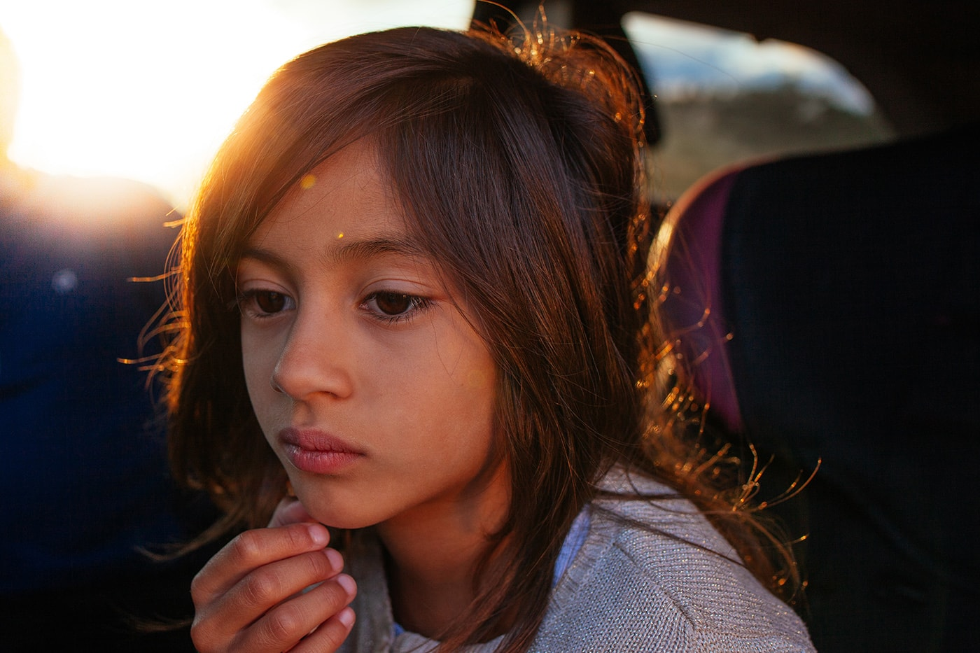 A portrait of a young girl staring off camera with her hand touching her chin.
