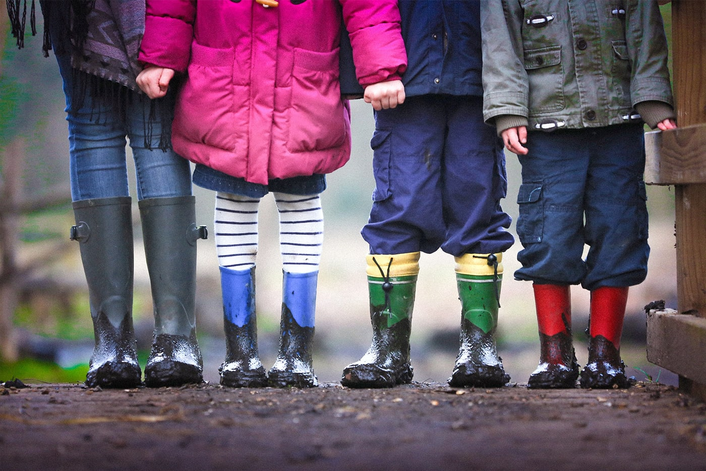 4 young children with muddy boots standing in a row