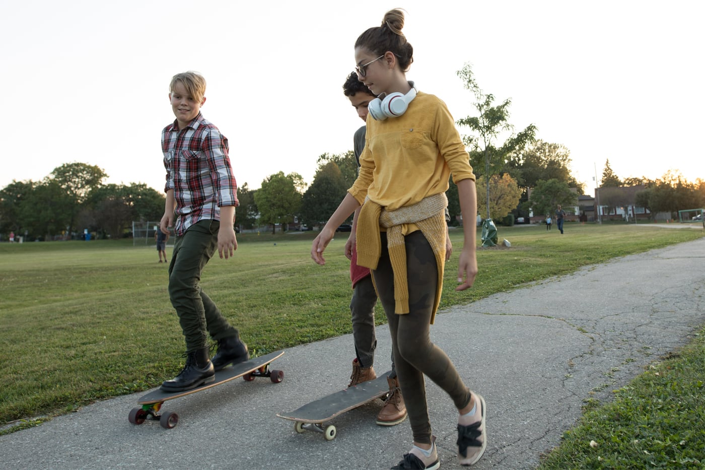 3 teenagers skateboarding in a park at dusk