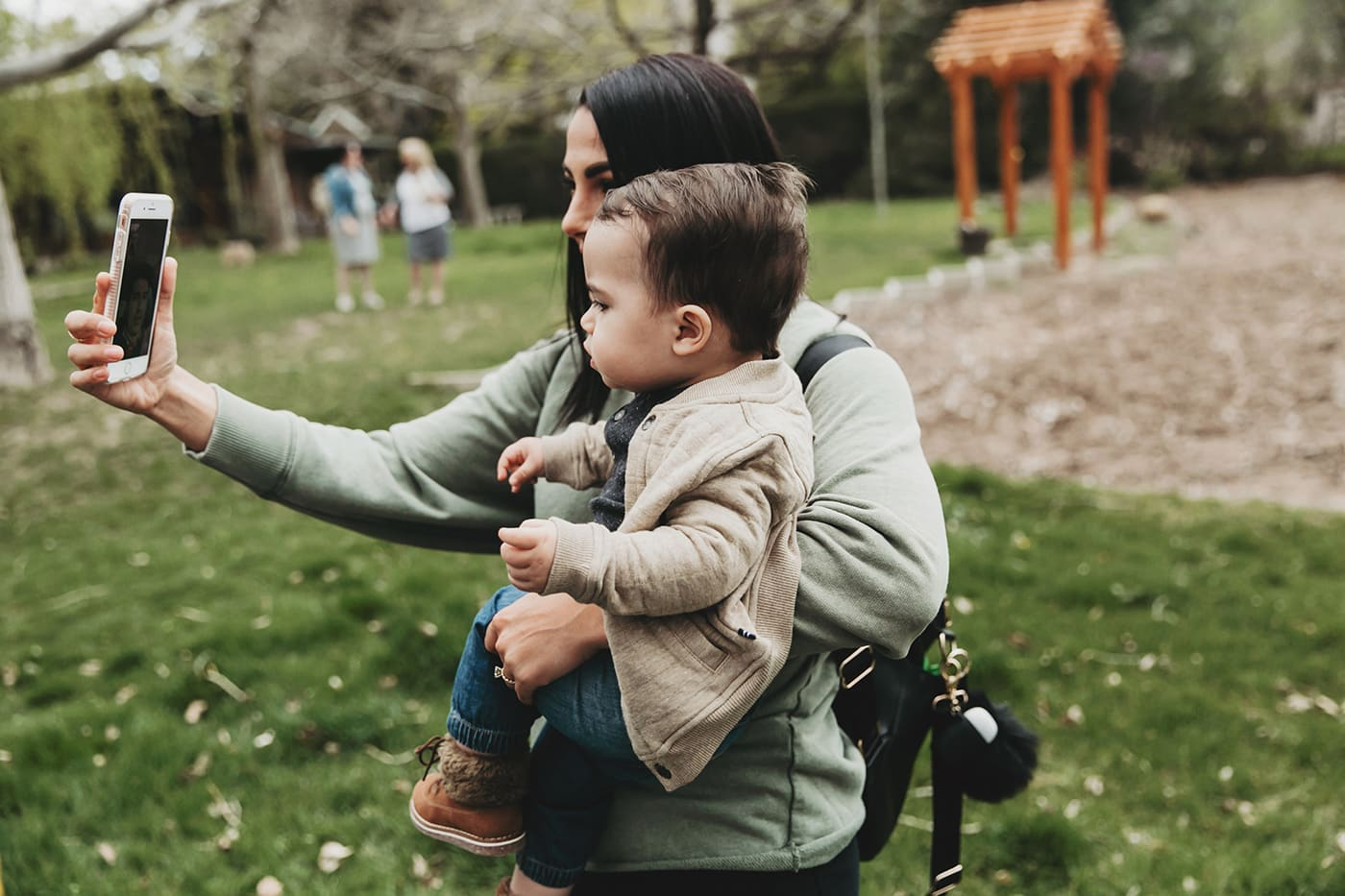 Mother holding toddler son in arms while taking a selfie together in a grassy park