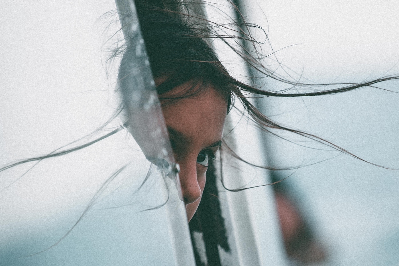 Young girl looking somber with head part way out an open car window with hair blowing in the wind. Face is obscured by the window and we only see one eye.