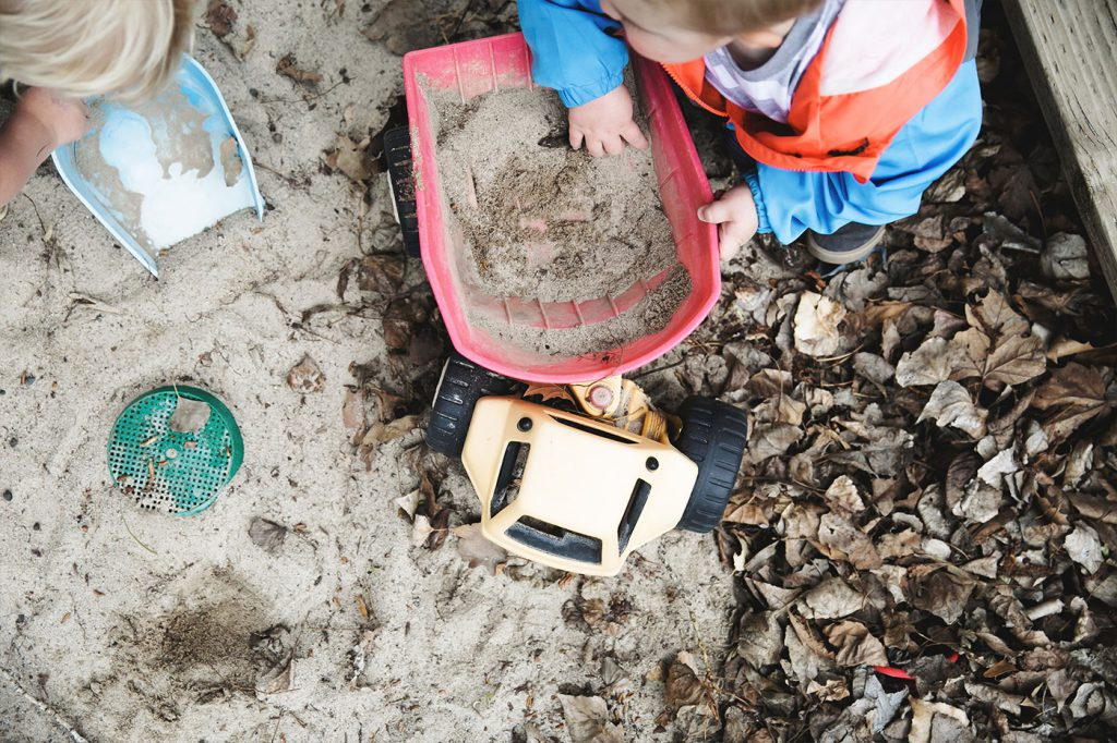 A boy and a Girl playing with shovels and trucks in the sand