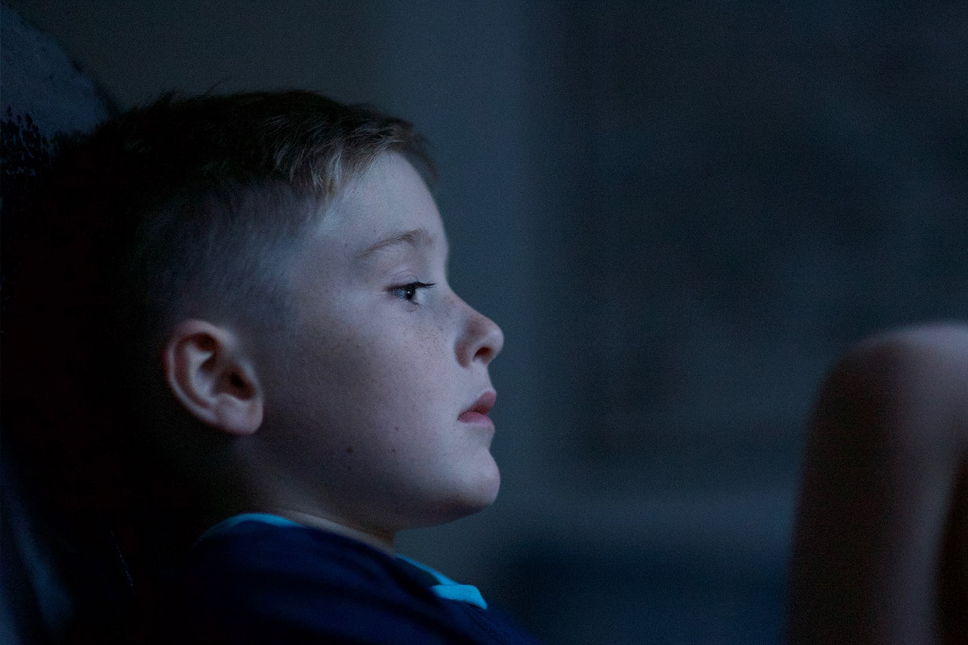 Somber child looking off toward a light or window