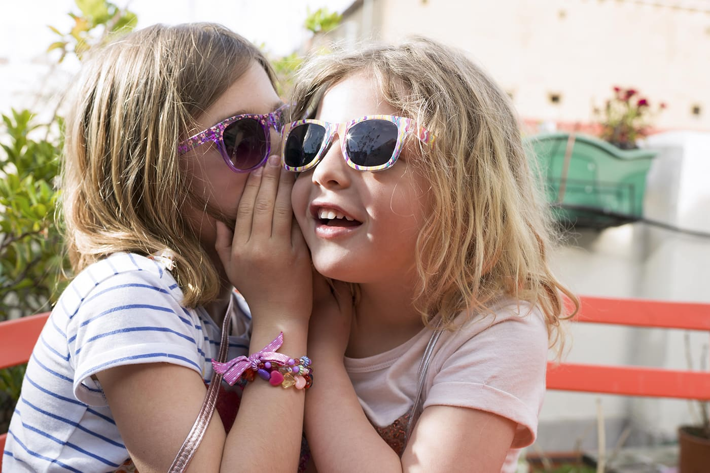 2 young girls wearing sunglasses in an outside garden telling secrets to each other.