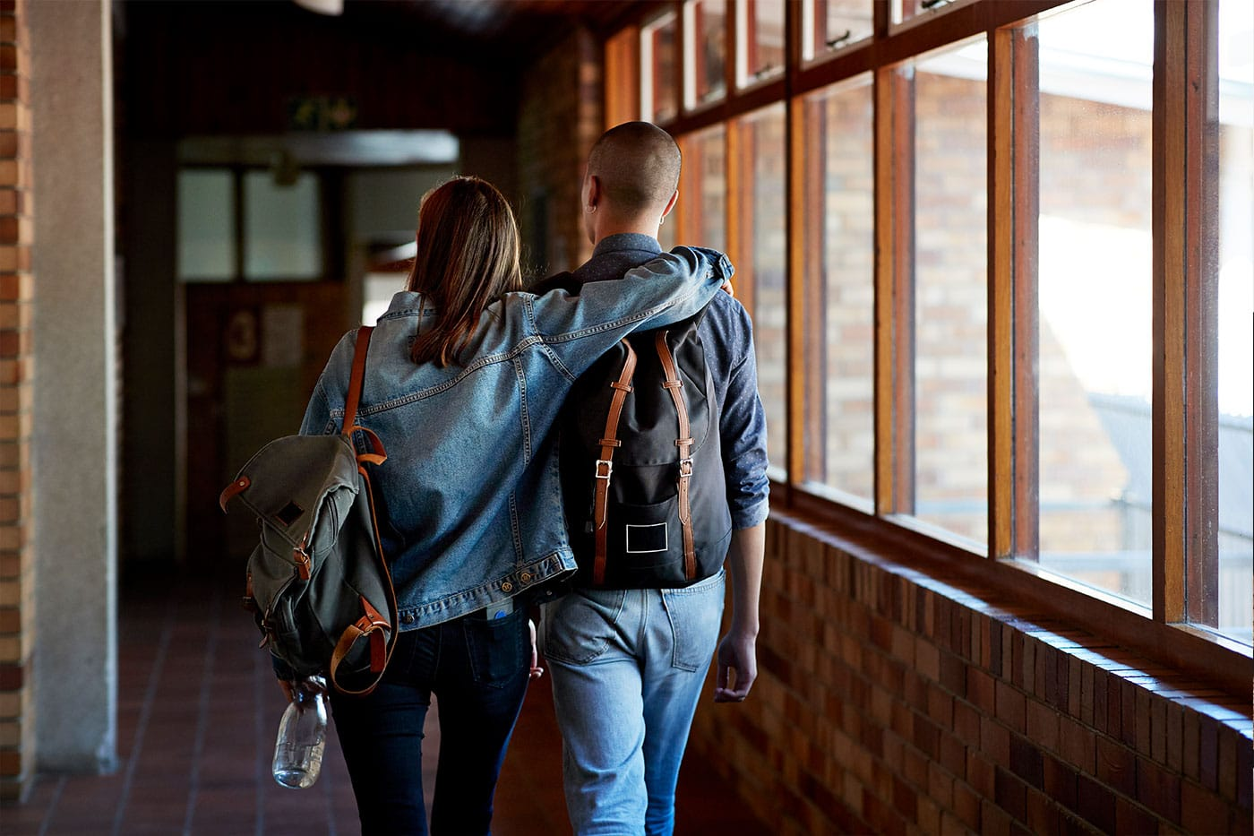 Male and Female college freshman walking in a corridor at their University