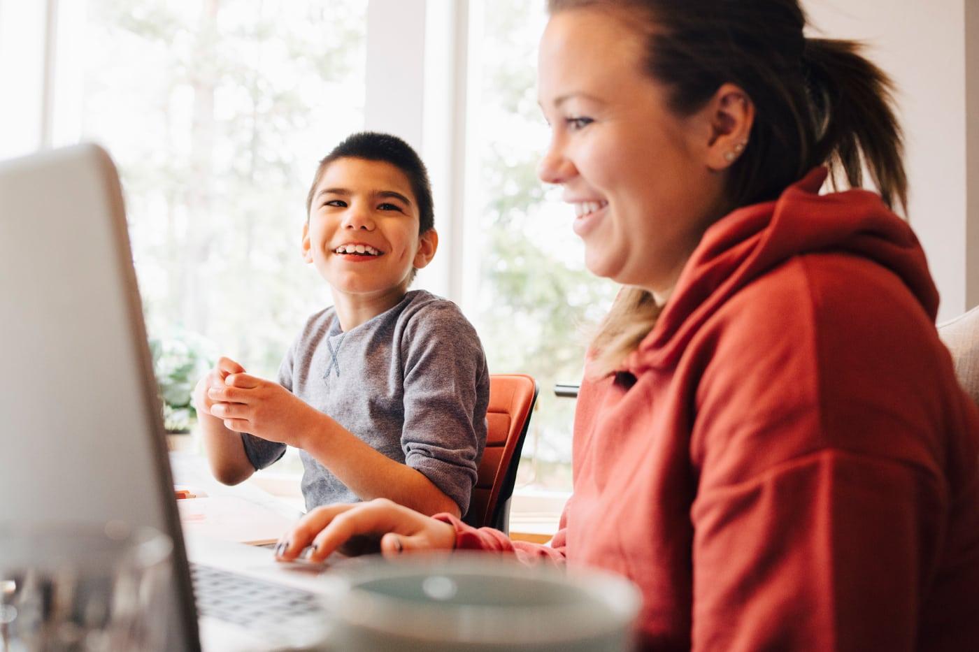 Mutter mit autistischem Sohn sitzt vor dem Computer