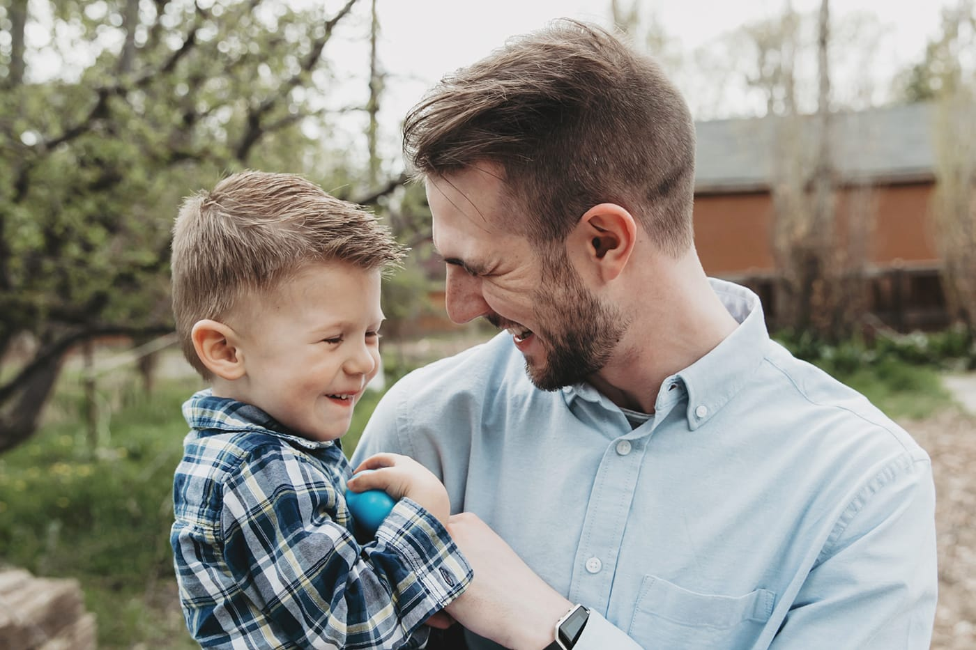 Father holding his toddler son and tickling him and laughing together