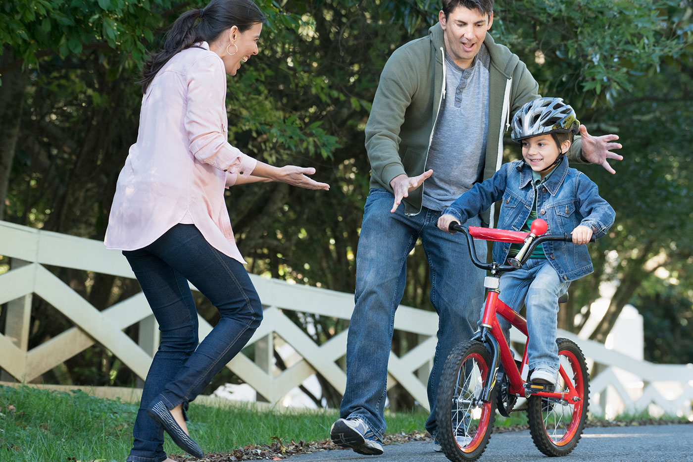 Hispanic mother and father celebrating their son riding his bike.