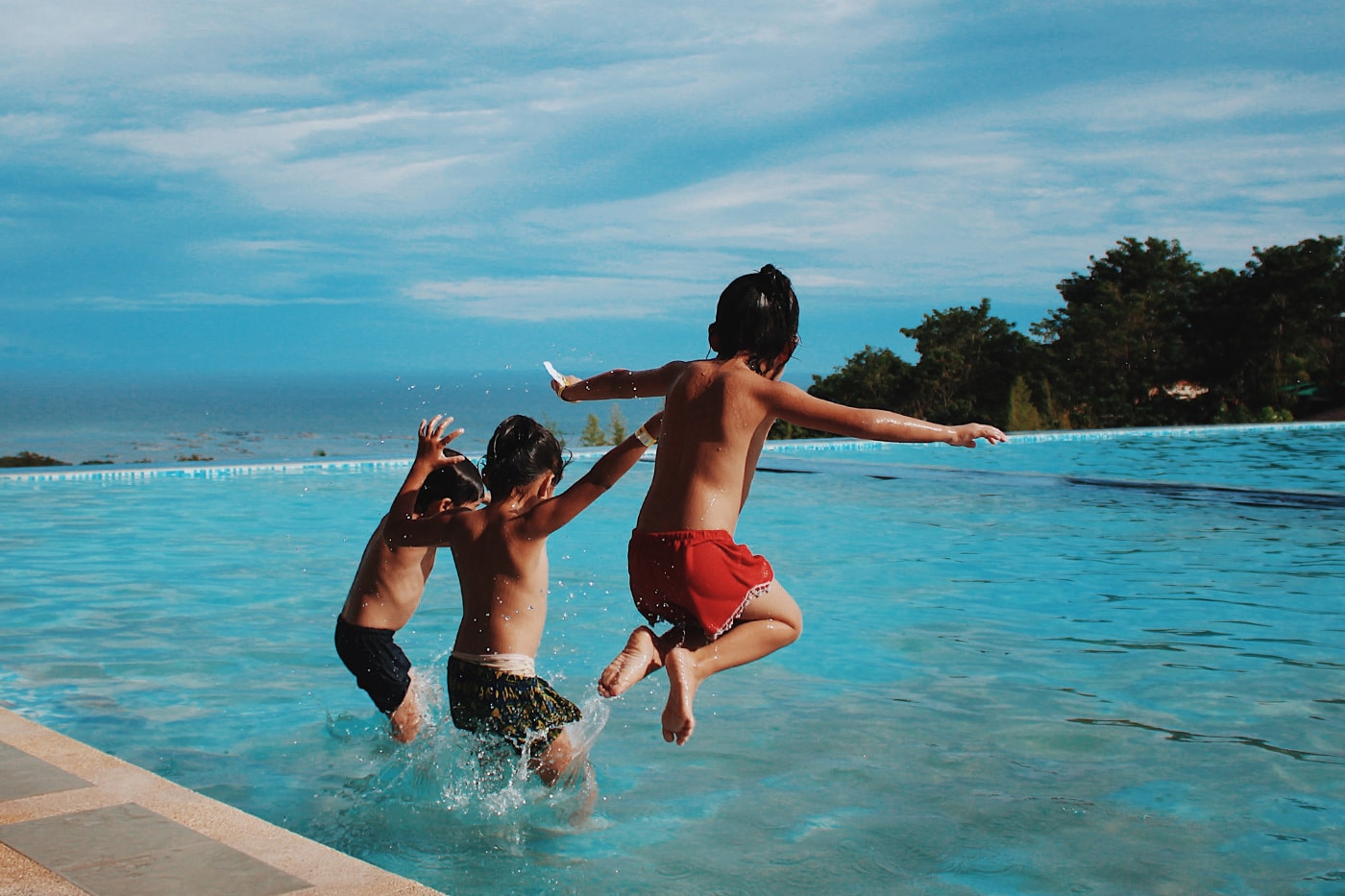 3 boys jumping into a swimming pool overlooking the ocean in summer