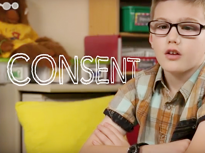 a boy wearing black glasses talking about consent