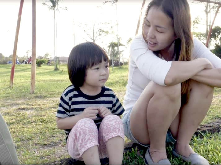 asian mom and a girl talking to each other in the park