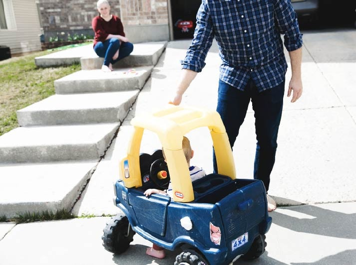 little boy riding a toy car and his dad helping him playing