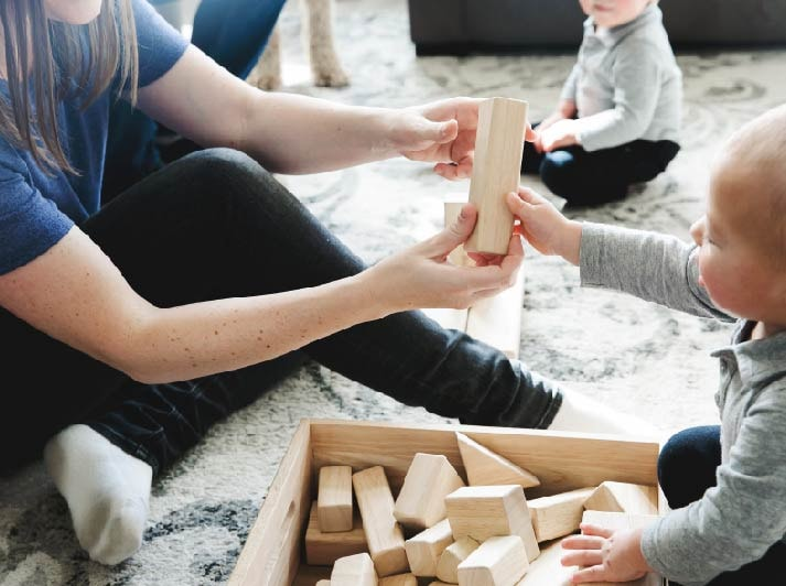 a woman playing wood blocks with a baby