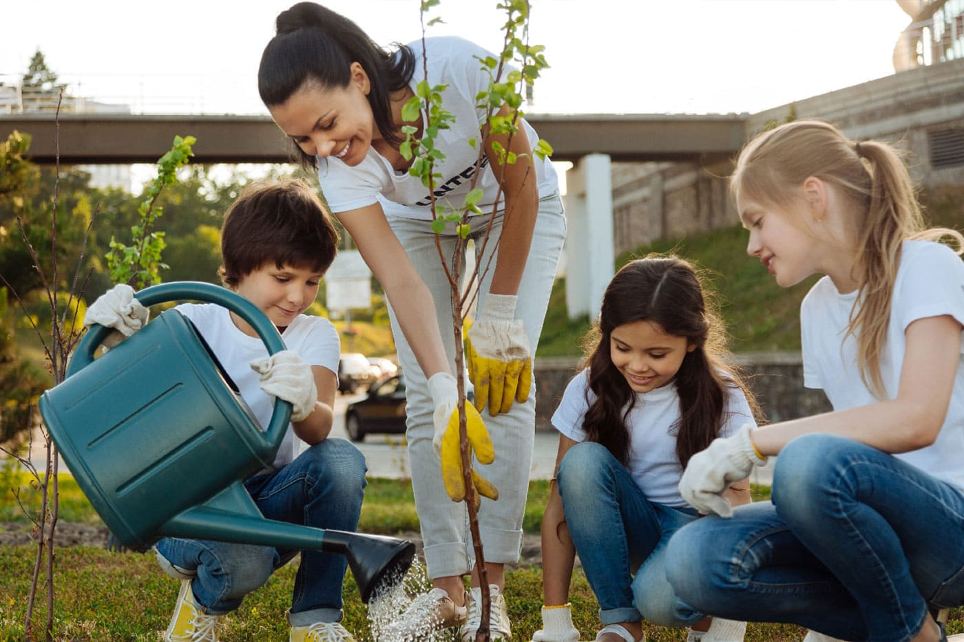a mom and three kids planting and gardening