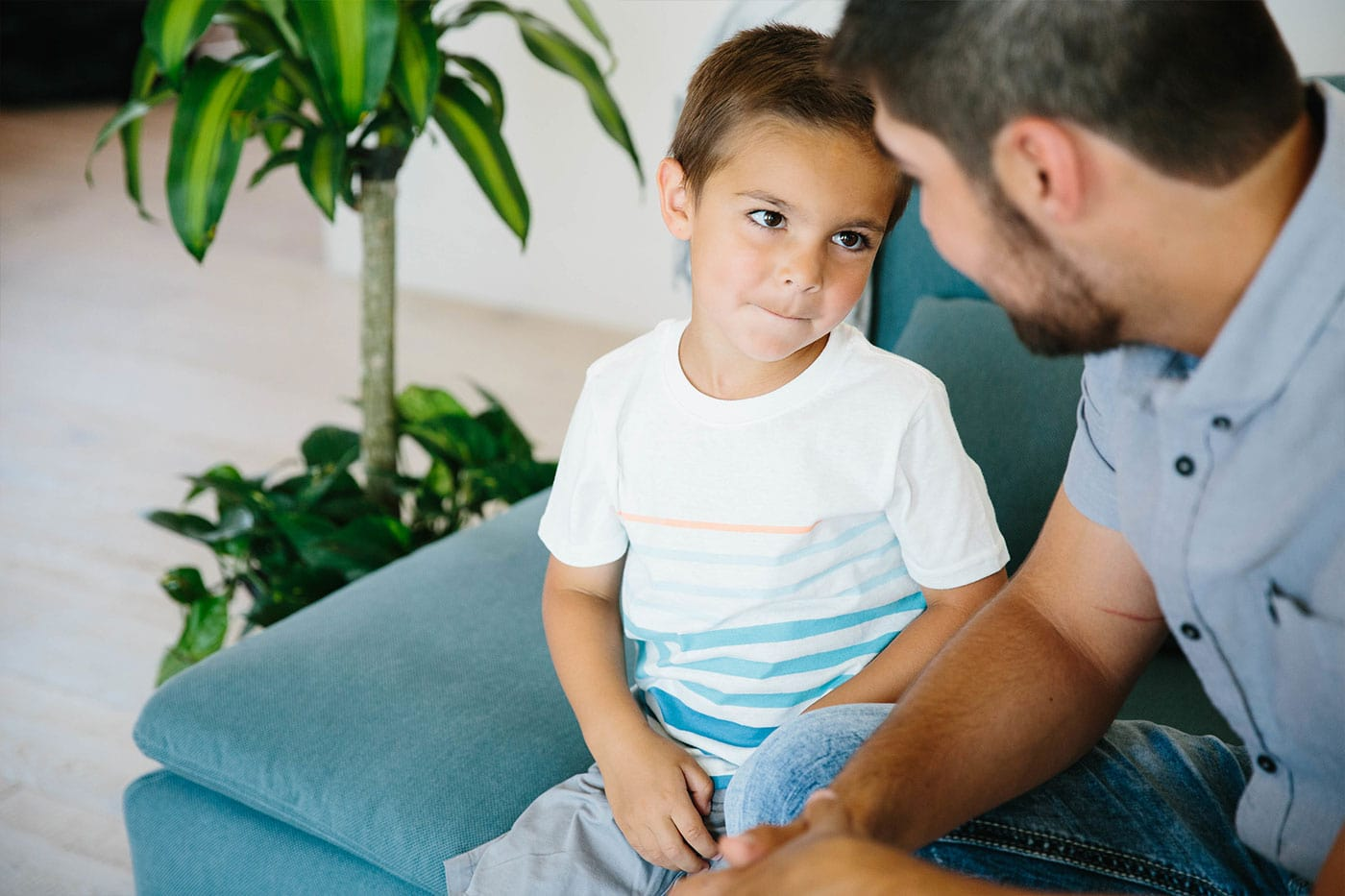 Father and son sitting on the sofa talking. The son has a mischievous look on his face but looking intently at his father.
