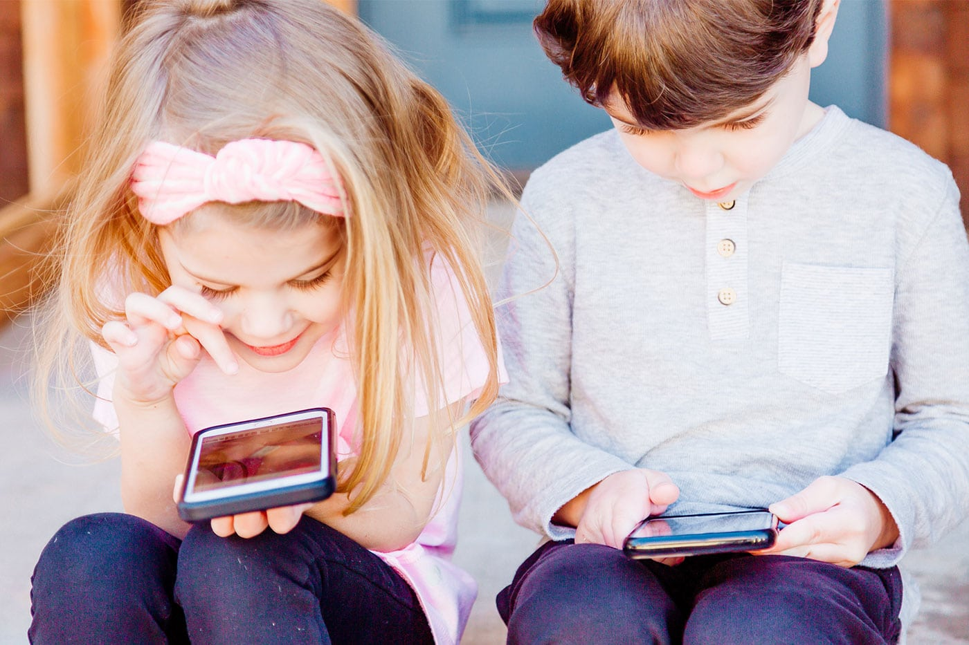 Two kids playing on their phones.