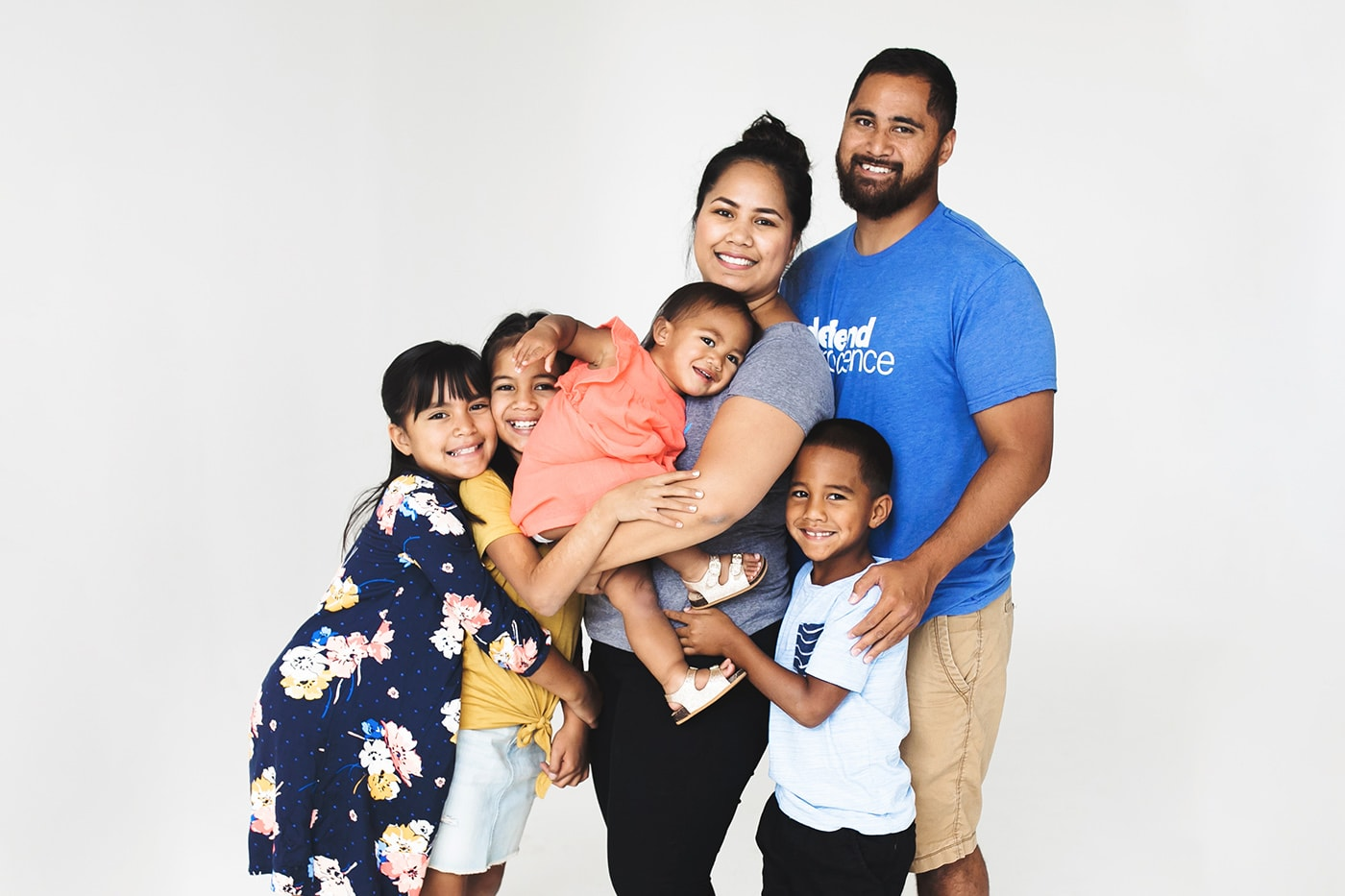 A blended hispanic family in a white studio hugging and smiling