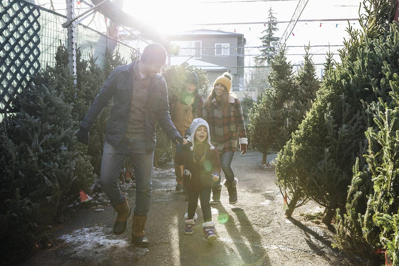 Familie kauft einen Weihnachtsbaum auf dem Weihnachtsmarkt